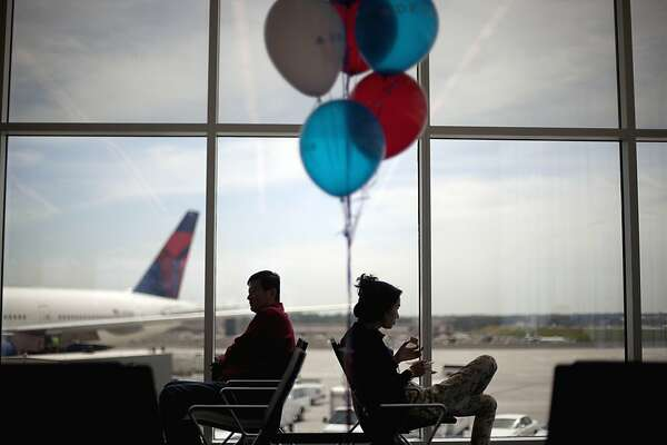 Passengers wait to board a plane to Tokyo, the first flight to leave out of the new Maynard Holbrook Jackson Jr. International Terminal at Atlanta's airport on the first day it begins operating flights Wednesday, May 16, 2012, in Atlanta. (AP Photo/David Goldman)