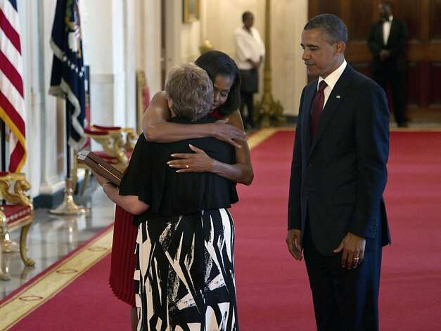 First lady Michelle Obama hugs Rose Mary Sabo-Brown after President Barack Obama awarded posthumously the Medal of Honor to Sabo-Brown, widow of Specialist Leslie H. Sabo, Jr., US Army, during a ceremony in the East Room of the White House in Washington, Wednesday, May 16, 2012. Sabo was killed in 1970 in Cambodia during the Vietnam War. (AP Photo/Carolyn Kaster) Photo: Carolyn Kaster, Associated Press