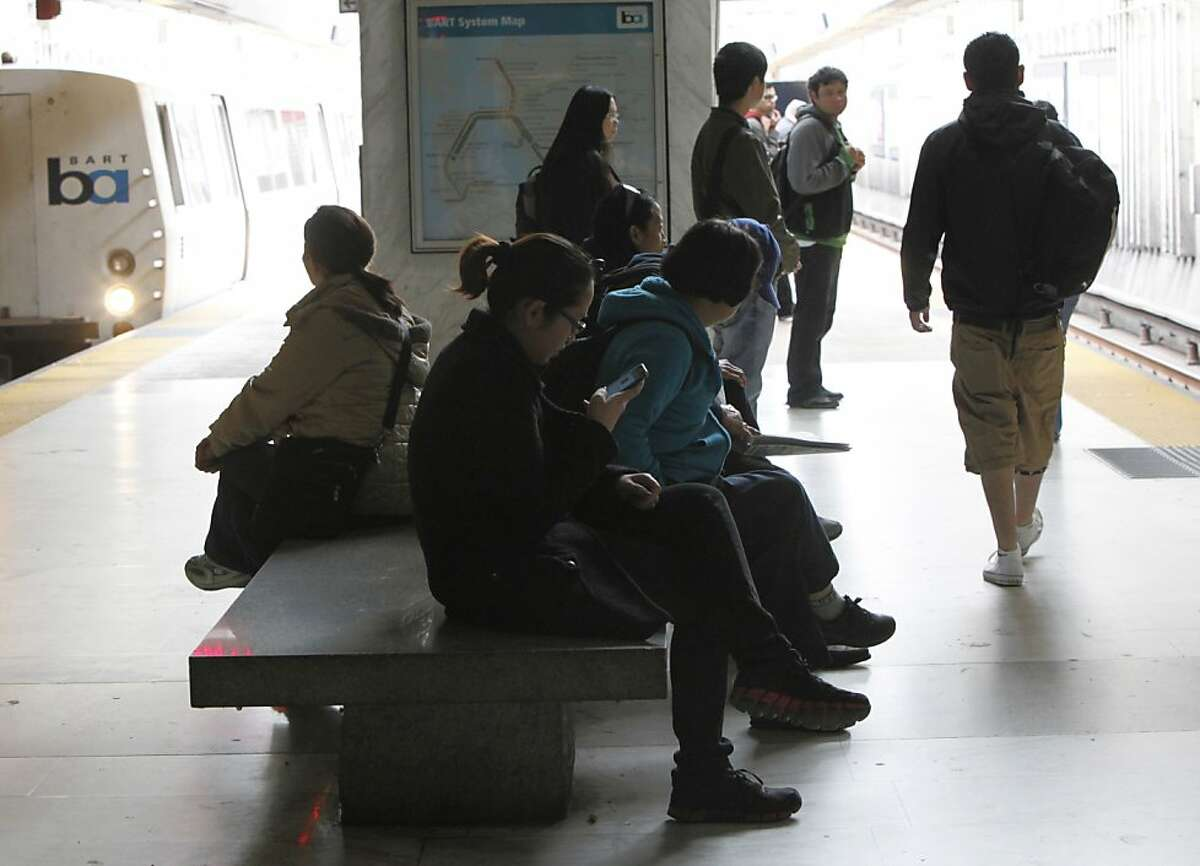 A woman looks at her phone before getting on BART at the Balboa Park Station in San Francisco, Calif., Tuesday May 15th, 2012.