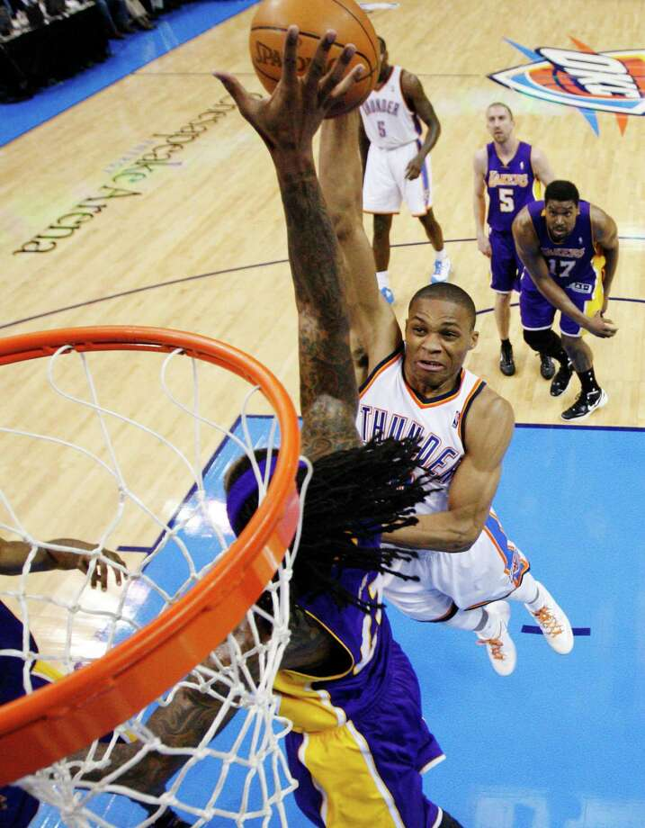 Oklahoma City Thunder guard Russell Westbrook, right, shoots over Los Angeles Lakers center Jordan Hill, left, in the second quarter in Game 2 of an NBA basketball playoffs Western Conference semifinal, in Oklahoma City on Wednesday, May 16, 2012. Oklahoma City won 77-75. (AP Photo/Sue Ogrocki, Pool) Photo: Sue Ogrocki, Associated Press / AP Pool
