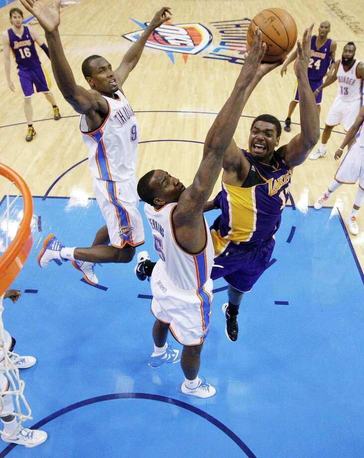 Los Angeles Lakers center Andrew Bynum, right, shoots in front of Oklahoma City Thunder forward Serge Ibaka, left, and center Kendrick Perkins, center, in the fourth quarter in Game 2 of an NBA basketball playoffs Western Conference semifinal, in Oklahoma City on Wednesday, May 16, 2012. Oklahoma City won 77-75. (AP Photo/Sue Ogrocki, Pool) Photo: Sue Ogrocki, Associated Press / AP Pool