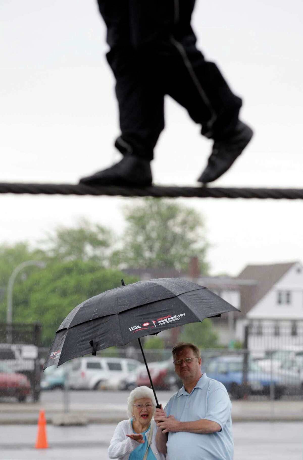 Nik Wallenda performs a walk on a tightrope in the rain as people watch during training for his walk over Niagara Falls in Niagara Falls, N.Y., Wednesday, May 16, 2012.