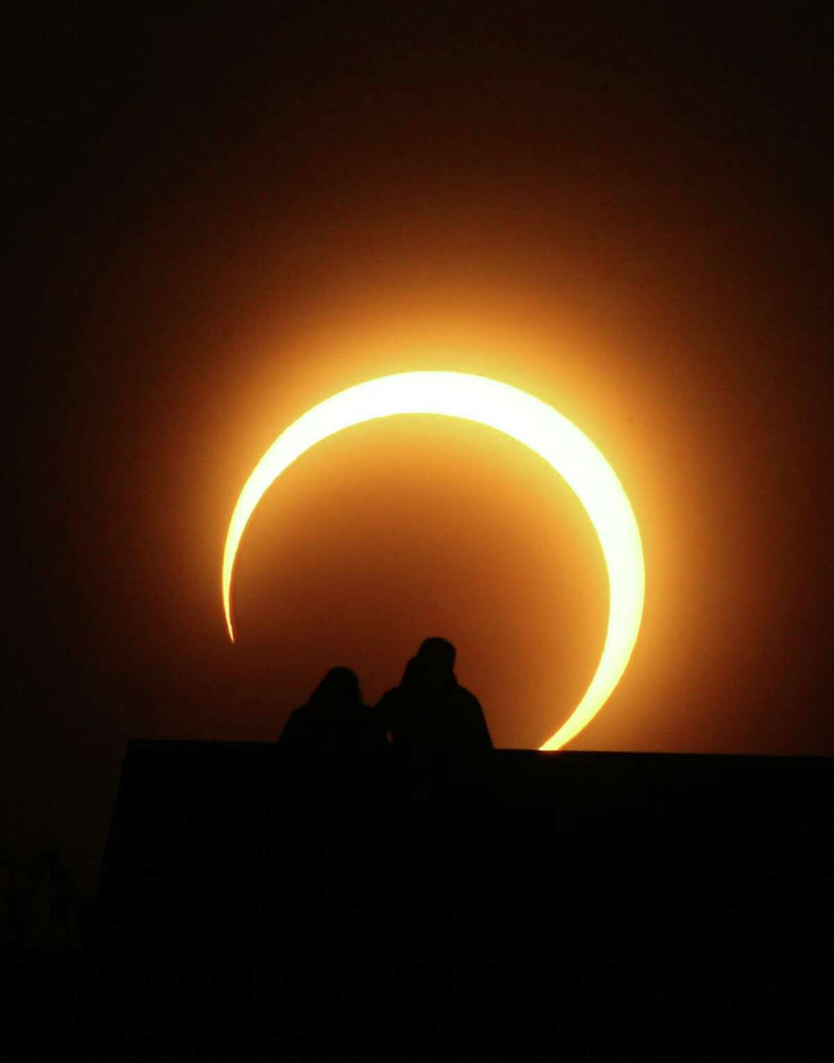 A Chinese couple watches the solar eclipse over Zhengzhou, central China's Henan province on Jan.15, 2010. A solar eclipse that reduced the sun to a blazing ring surrounding a somber disk plunged millions of people in Africa and Asia into an eerie semi-darkness, as the spectacle, visible in a roughly 300-kilometere (185-mile) band running 12,900 kilometers (8,062 miles) across the globe, set a record for the longest annular eclipse that will remain unbeaten for more than a thousand years. AFP PHOTO