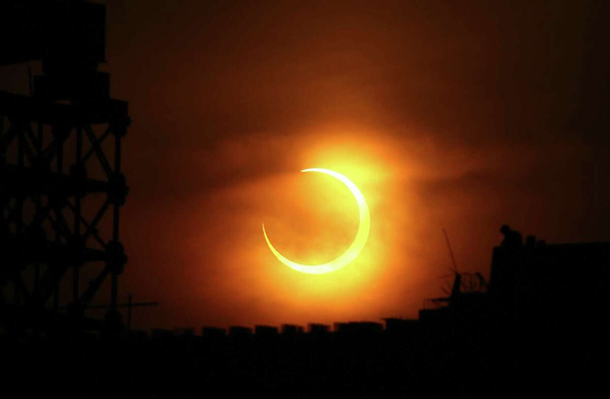 A solar eclipse appears over Zhengzhou, central China's Henan province on Jan.15, 2010. A solar eclipse that reduced the sun to a blazing ring surrounding a somber disk plunged millions of people in Africa and Asia into an eerie semi-darkness, as the spectacle, visible in a roughly 300-kilometer (185-mile) band running 12,900 kilometers (8,062 miles) across the globe, set a record for the longest annular eclipse that will remain unbeaten for more than a thousand years. AFP PHOTO