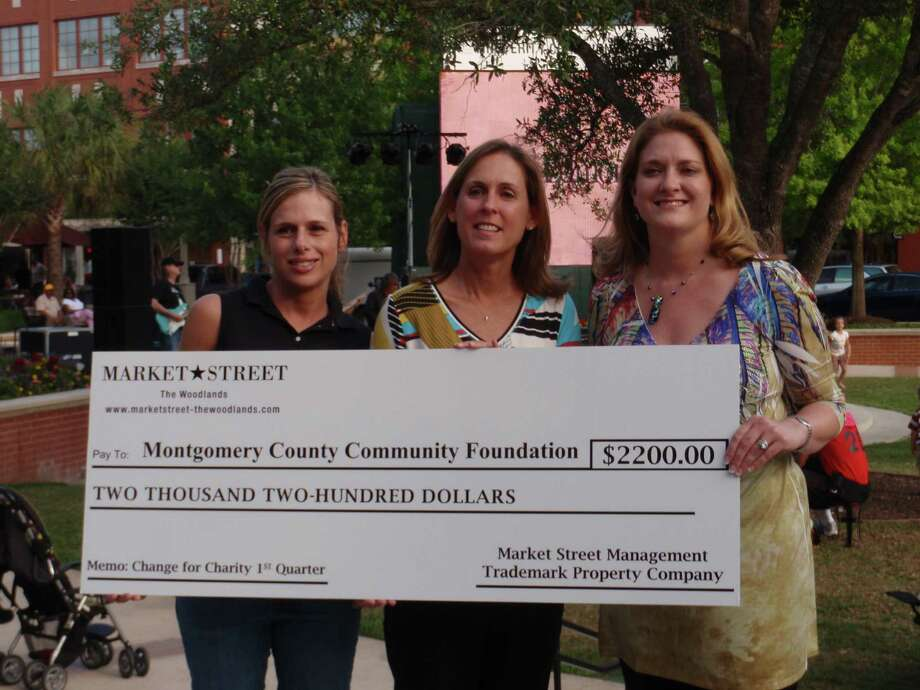 Shannon Kidd (center), director of the Montgomery County Community Foundation, accepts a donation from Dana Pritchard of The Woodlands Car Club (left) and Jenny Taylor of Market Street – The Woodlands.