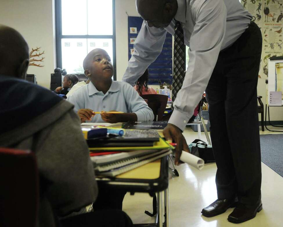 Second-grader Mehki Kersey, left, talks with principal Anthony Clement during the first day of school at Schuyler Achievement Academy elementary school last fall. (Paul Buckowski / Times Union archive)