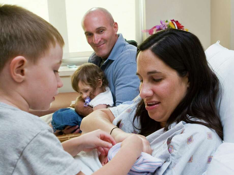 Stamford Police officer Troy Strauser with his family at Stamford Hospital in 2009 after his wife gave birth to their daughter, Sadey. Strauser was critically injured Thursday, May 17, 2012 after falling 20 feet from a bridge abutment while chasing a robbery suspect in Norwalk, Conn., early Thursday morning. Also photographed are Strauser's wife, Torey, and children Zachary, then 3, and Zoe, then 1. The family had the baby the hospital three years ago after being escorted there by a state trooper when Strauser was in labor and stuck in the morning traffic. Photo: Kerry Sherck / Stamford Advocate