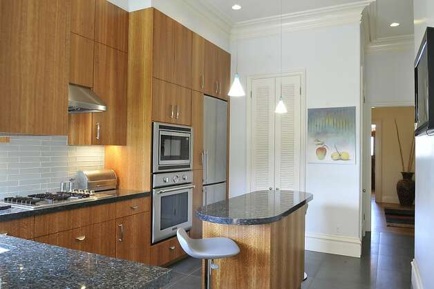 The contemporary kitchen has granite countertops and glass tile. Photo: Garylee Hall