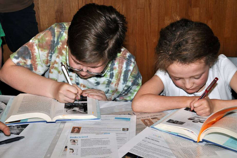 Corey Haas and Hannah Sames, two local children featured in the book, sign their photographs at a book talk in Schenectady in April. Photo credit Sandy Andersen