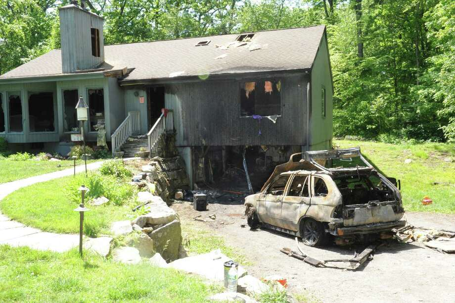 A car fire in a garage damaged a home at 5 Steep Hollow Lane in Cos Cob, pictured Thursday, May 17, 2012. Two firefighters were hospitalized with minor injuries suffered while battling the fire Wednesday. The homeowners were not home at the time of the fire, but two of their dogs were rescued, fire officials said. Photo: Helen Neafsey / Greenwich Time