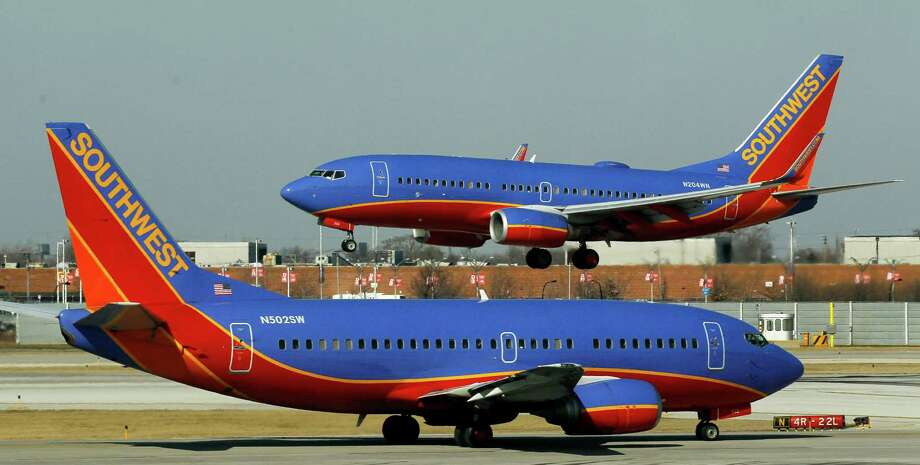 FILE - In this Feb. 9, 2012 file photo, a Southwest Airlines Boeing 737 waits to take off at Chicago's Midway Airport as another lands. Southwest Airlines says it made $98 million in the first quarter of 2012, helped by one-time gains on fuel-hedging contracts. Photo: AP
