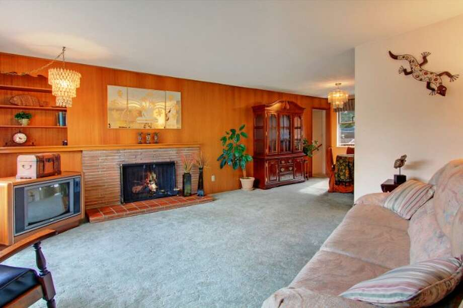 Our first home, 10505 8th Ave. N.W., totally embraces its retro style. The listing notes that the 1,910-square-foot rambler, built in 1953, features three bedrooms, two with shag carpeting and the third with lush pink carpeting, 1.75 bathrooms, 'classic wood paneled walls,' a 'fun retro kitchen' and a leather-covered bar. It's listed for $369,950. Photo: Courtesy Greg & Janet Buehler/Windermere Real Estate