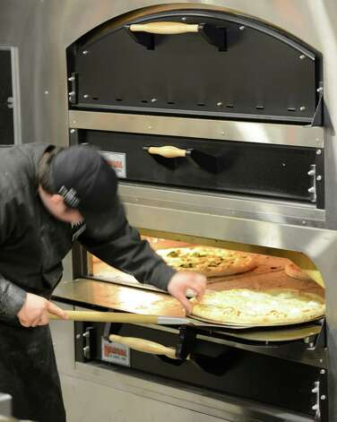 A culinarian makes pizza at the Global Cafe in the Global Foundries complex in Malta, N.Y. May 14, 2012. (Skip Dickstein / Times Union) Photo: SKIP DICKSTEIN / 2012