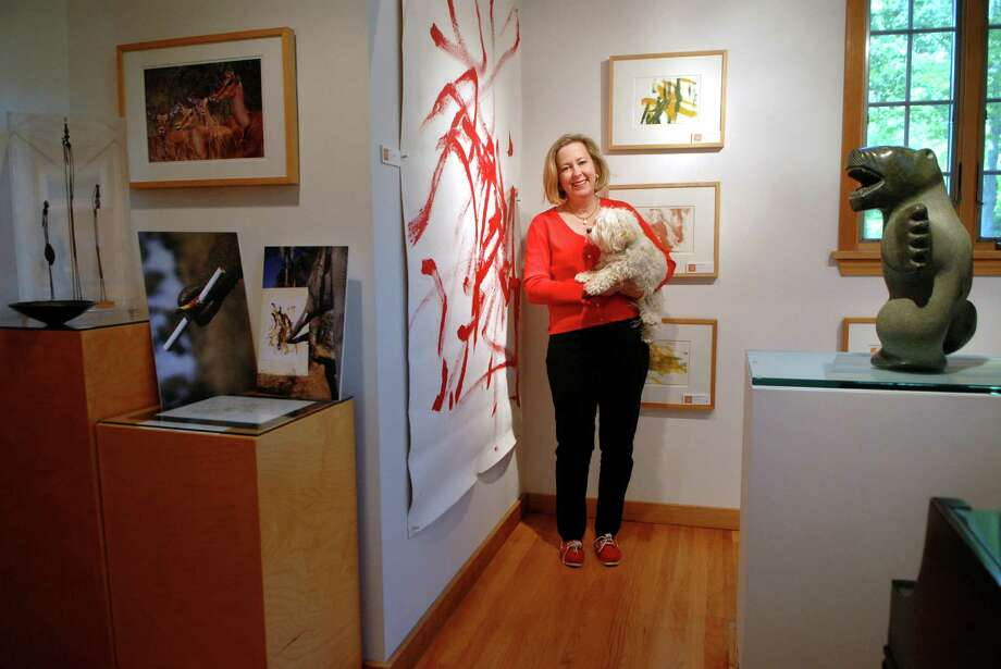 """Elizabeth Ball, the CEO of TFI Envision, holds her dog """"Honey"""" in her gallery, the Pierce-Ball Gallery in Stamford, Conn. on Saturday May 12, 2012 surronded by paintings done by elephants. Photo: Dru Nadler / Stamford Advocate Freelance"""