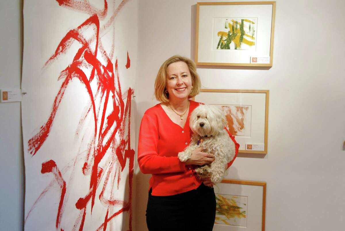 Elizabeth Ball, the CEO of TFI Envision, holds her dog