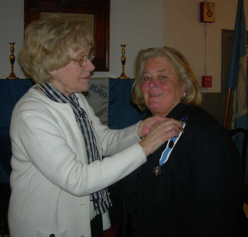Pamela Hutch, left, outgoing regent of the Eunice Dennie Burr chapter of the Daughters of the American Revolution, pins the regent's pin on the her successor, Cathy Tymniak. Photo: Contributed Photo / Fairfield Citizen contributed