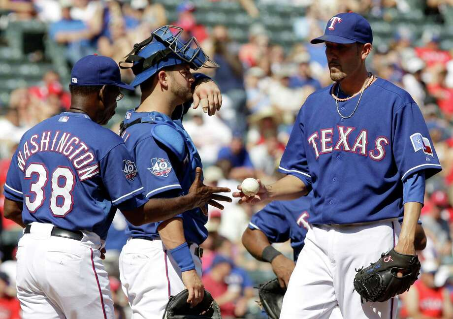 Texas Rangers manager Ron Washington (38) pulls pitcher Mike Adams, right, as catcher Mike Naploli looks on after Oakland Athletics Kila Ka'aihue's RBI-single in the 10th inning of the baseball game on Thursday, May 17, 2012, in Arlington, Texas. The Athletics won 5-4. Photo: AP