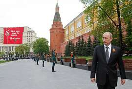 Russian President Vladimir Putin, right, leaves a wreath laying ceremony at the Tomb of Unknown Soldier on the eve of Victory Day celebration in Moscow, Russia, Tuesday, May 8, 2012. Russia marking the surrender of Nazi Germany in World War II, is the centerpiece of Russia's most solemn secular holiday.(AP Photo/RIA-Novosti, Dmitry Astakhov, Presidential Press Service)