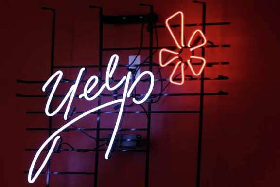 FILE - In this Oct. 26, 2011 file photo, the logo of the online reviews website Yelp is shown in neon on a wall at the company's new Manhattan offices in New York. Online reviews site Yelp is expected to price its initial public offering of stock on Thursday , March 1, 2012, and become the latest in a long line of social websites going public.