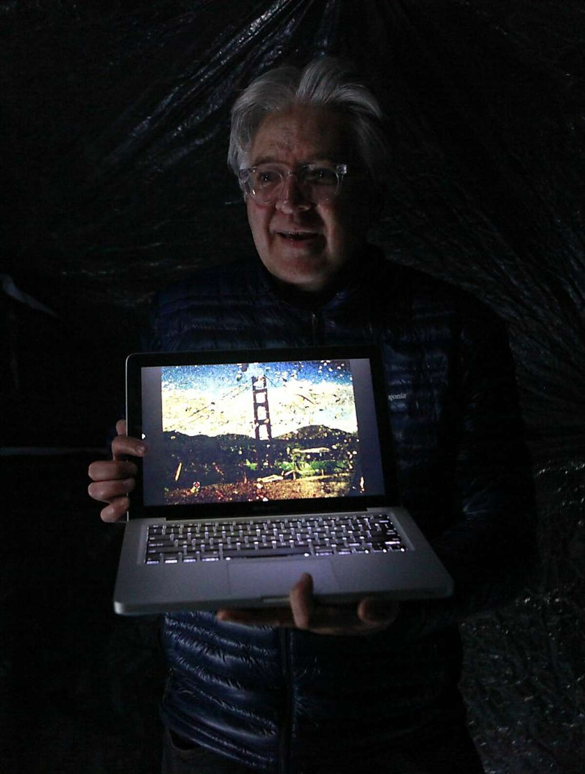 Abelardo Morell, shows what one of his final images looks like on his computer. Abelardo came out from Boston to demonstrate his portable camera obscura in a tent, which he will later set up inside the brick barracks during the International Orange exhibition that will take over Fort Point National Historic Site as part of the 75th anniversary celebration of the Golden Gate Bridge. This demonstration took place in San Francisco, California on Friday, April 13, 2012.
