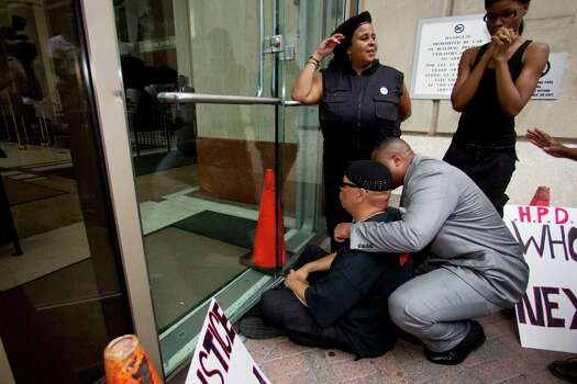Kofi Taharka, left, and Krystal Mohammed demonstrate at the door of the Harris County Criminal Justice Center Thursday, May 17, 2012, in Houston. The demonstrators marched in response to the not guilty verdict handed down by a jury Wednesday in the case against former Houston Police officer Andrew Blomberg. Blomberg had been accused of official oppression for his role in the 2010 beating of Chad Holley, which was caught on videotape. Photo: Brett Coomer, Houston Chronicle / © 2012 Houston Chronicle
