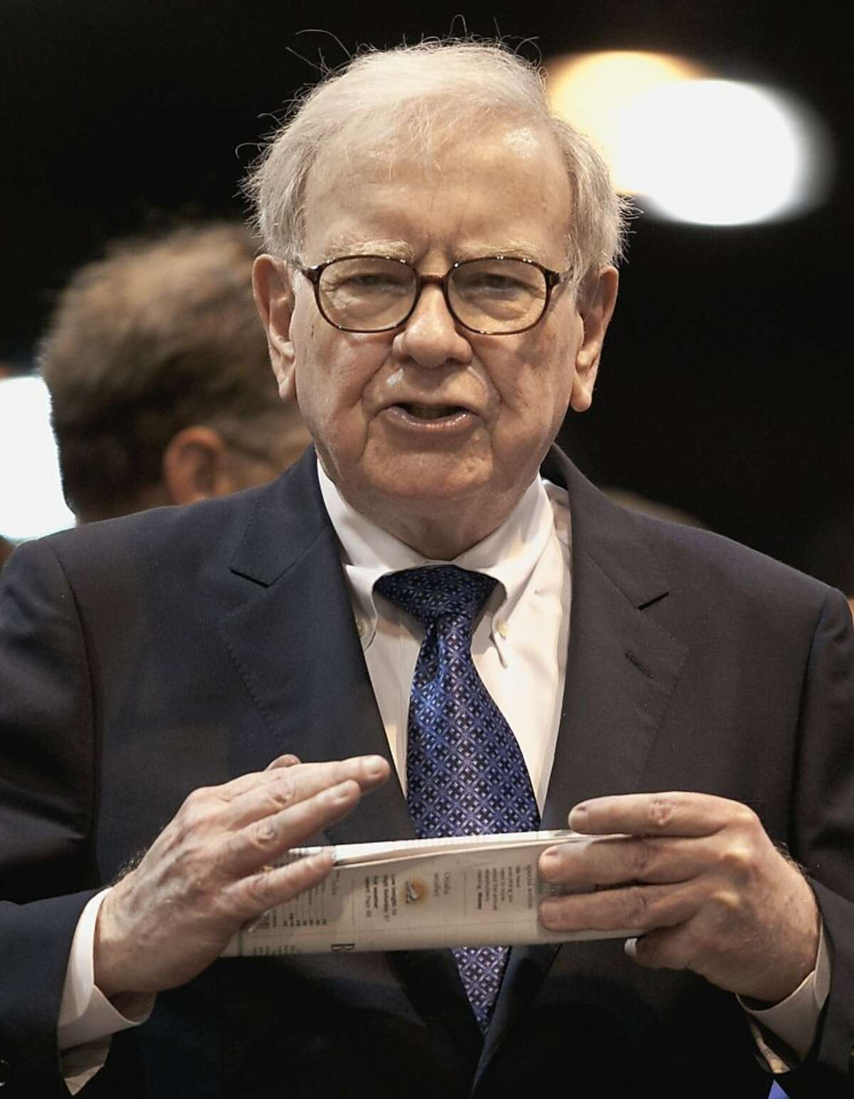 In this May 5, 2012 photo, Warren Buffett, chairman and CEO of Berkshire Hathaway, holds a newspaper as he participates in a newspaper throwing competition prior to the Berkshire Hathaway shareholders meeting in Omaha, Neb. On Thursday, May 17, 2012, Buffett's company Berkshire Hathaway agreed to buy 63 papers from Media General Inc. The Richmond, Va.-based Media General says the $142 million deal includes the Richmond Times-Dispatch and the Winston-Salem Journal. The company is selling all its papers except those in Tampa, Fla., most importantly the Tampa Tribune. (AP Photo/Nati Harnik)
