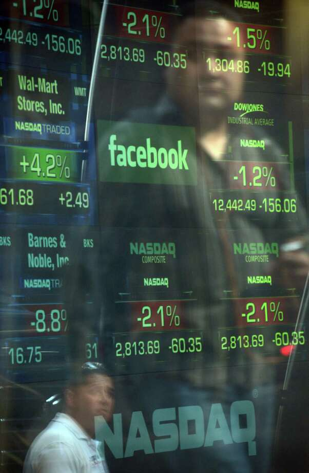 A Nasdaq screen features the Facebook logo on Thursday. At the IPO price, Mark Zuckerberg's share comes in at $20 billion. Photo: EMMANUEL DUNAND / AFP