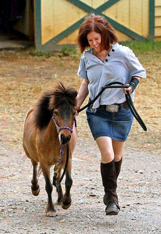 """Don't call him 'miniature':Sheelagh Cafferkey runs with Cole, who no doubt considers himself a perfectly normal equine specimen at Show Me Farm North in Ball Ground, Ga. It's those """"giant horses"""" who let people sit on them who are weird. Photo: Jason Getz, McClatchy-Tribune News Service"""