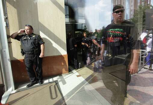 A Sheriffs Officer, along with other law enforcement, file in the lobby of the Harris County Criminal Courthouse as protesters outside ask to see District Attorney Pat Lykos. Photo: Mayra Beltran, Houston Chronicle / Houston Chronicle