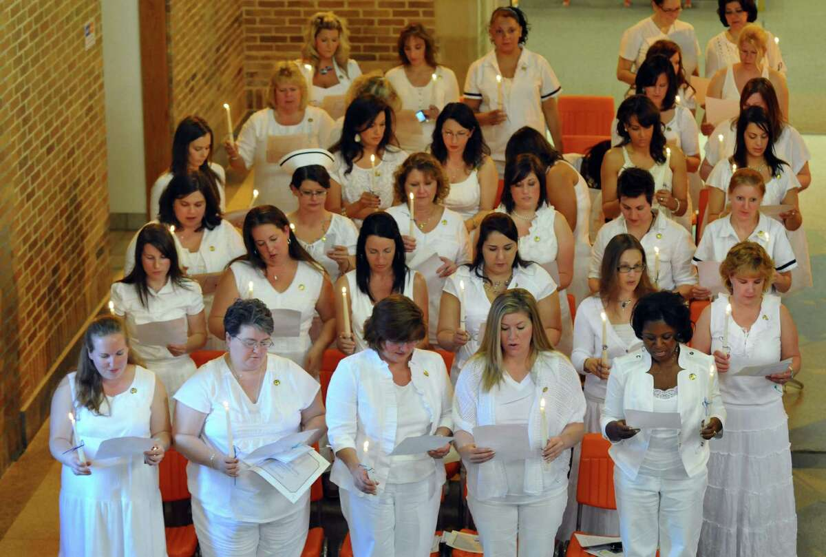 Maria College senior nursing graduates recite the Florence Nightingale Pledge during a candlelight ceremony to signify their commitment to the nursing profession, during the Maria College annual White Tea & Pinning ceremony, on Thursday May 17, 2012 in Albany, NY. Graduation will be held on Sunday. (Philip Kamrass / Times Union )