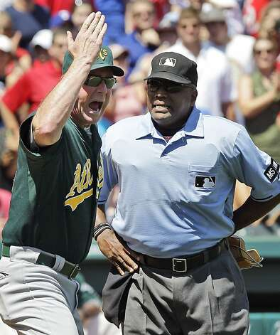 Oakland Athletics manager Bob Melvin, left, argues with home plate umpire Laz Diaz (63) about a call on a bunt by Texas Rangers' Elvis Andrus during the sixth inning of a baseball game Thursday, May 17, 2012, in Arlington, Texas. The Athletics won 5-4.  (AP Photo/LM Otero) Photo: LM Otero, Associated Press
