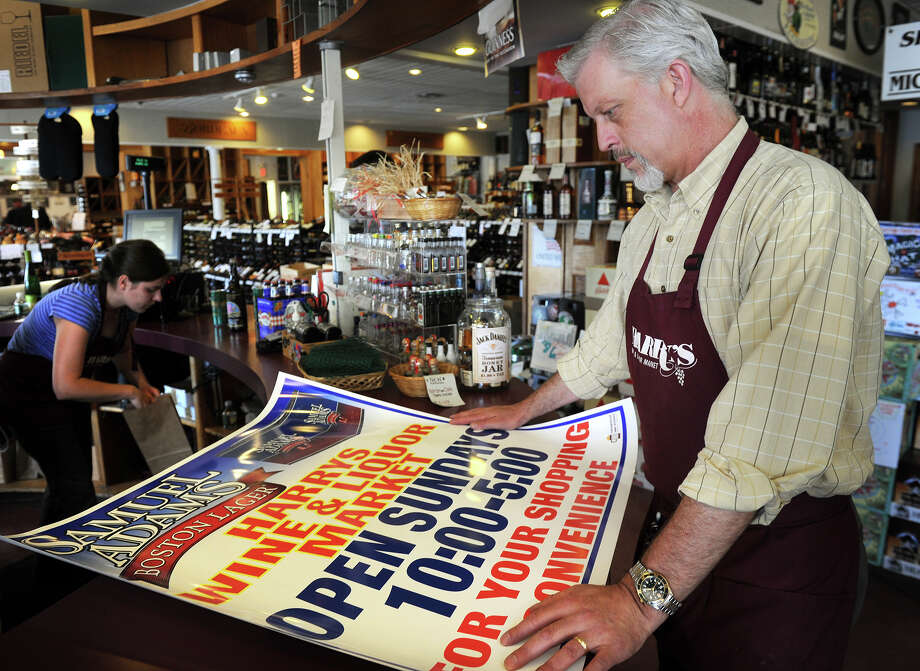 Proprietor Patrick Monteleone looks over one of his signs advertising new Sunday sales hours at Harry's Wine and Liquor at 2094 Post Road in Fairfield on Thursday, May 17, 2012. Photo: Brian A. Pounds / Connecticut Post
