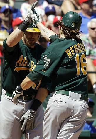 Oakland Athletics' Josh Reddick (16) celebrates with Jonny Gomes after Reddick's solo home run during the seventh inning of a baseball game against the Texas Rangers, Thursday, May 17, 2012, in Arlington, Texas. The Athletics won 5-4 in the 10th inning. (AP Photo/LM Otero) Photo: LM Otero, Associated Press