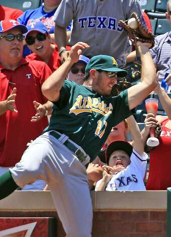 Fans react as Oakland Athletics first baseman Adam Rosales (17) catches the pop fly by Texas Rangers Ian Kinsler, not shown, during the first inning of a baseball game, Thursday, May 17, 2012, in Arlington, Texas. (AP Photo/LM Otero) Photo: LM Otero, Associated Press