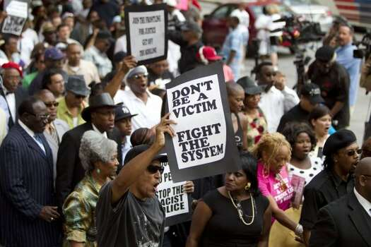 Demonstrators carry signs as they rally. (Brett Coomer / Houston Chronicle)
