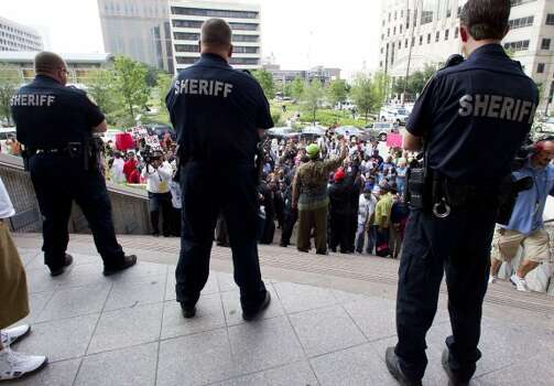 Harris County sheriff's deputies stand on the steps of courthouse as they watch over protesters. (Brett Coomer / Houston Chronicle)