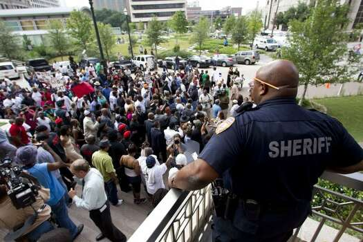An officer watching over the protest. (Brett Coomer / Houston Chronicle)