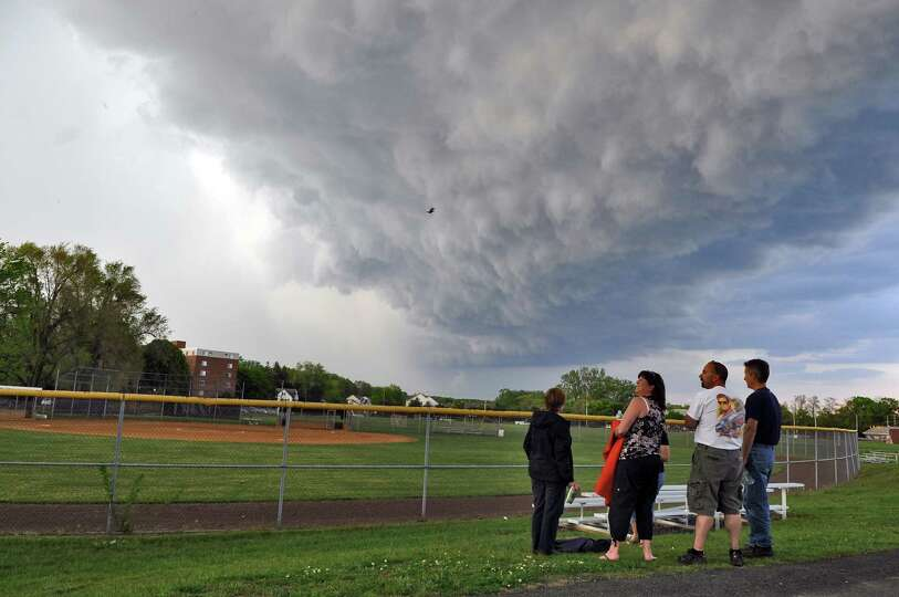 Lynn Hyde and her husband Chuck, center, watch a storm roll in as their daughter Paige's softball ga