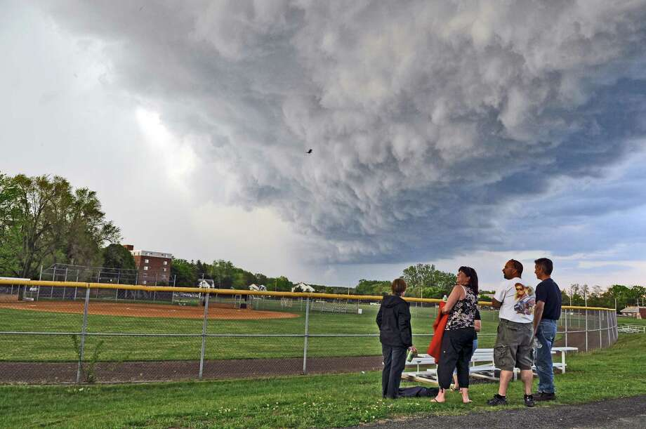 Lynn Hyde and her husband Chuck, center, watch a storm roll in as their daughter Paige's softball game with Columbia High School was delayed against Colonie High School on Wednesday May 16, 2012 in Colonie, NY.  The storm included rain, lightning and thunder.  Umpires eventually ruled the rain shortened game a four and a half inning 2-0 victory for Colonie.  (Philip Kamrass / Times Union ) Photo: Philip Kamrass / 00017717A