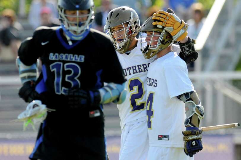 CBA's John Bassett (14), right, celebrates a goal with teammate Don Vivian (2) during their lacrosse