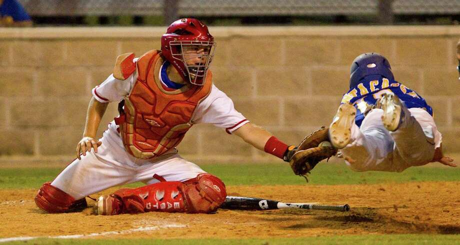 Tomball catcher Tyler Schulin tags out Klein's Andrew Santacroce on a throw from first baseman Spence Rahm to complete a double play and give the Cougars a 7-6 victory in Thursday night's Class 5A playoff game. Photo: Nick De La Torre / © 2012  Houston Chronicle