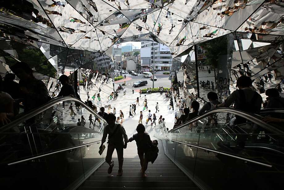 A couple enter a shopping complex in the Omotesando district of Tokyo, where Apple is building a store expected to open in March. Photo: Tomohiro Ohsumi, Bloomberg
