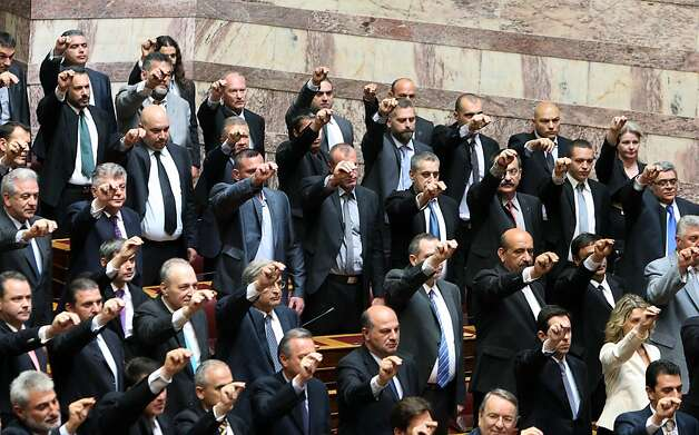 Members of parliament from the extreme right-wing Golden Dawn party, intermingled with other new lawmakers as they are sworn in during a ceremony at the Greek parliament in Athens, Thursday, May 17, 2012. Among the deputies to take their seats for a day are 21 from the Golden Dawn, which rejects the neo-Nazi label. It campaigned on pledges to rid Greece of immigrants and clean up neighborhoods. (AP Photo/Thanassis Stavrakis) Photo: Thanassis Stavrakis, Associated Press