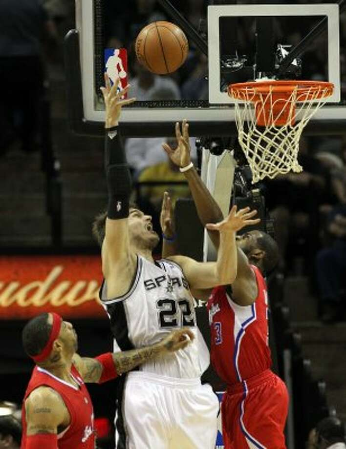 San Antonio Spurs' Tiago Splitter (22) shoots over  Los Angeles Clippers' Kenyon Martin (2) and  Los Angeles Clippers' Chris Paul (3) in the first half of game two of the Western Conference semifinals at the AT&T Center on Thursday, May 17, 2012. Kin Man Hui/Express-News (SAN ANTONIO EXPRESS-NEWS)