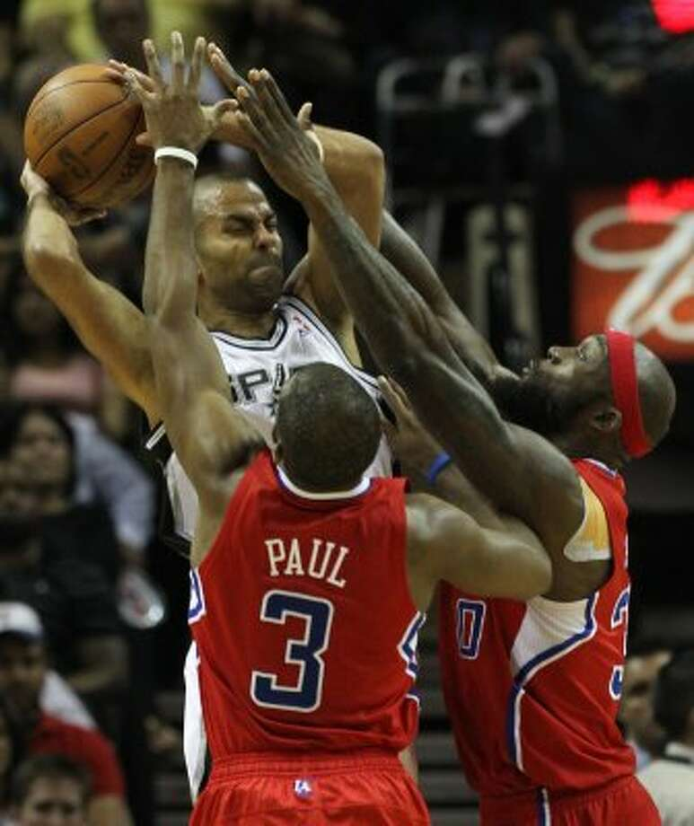 San Antonio Spurs' Tony Parker (9) is pressured by  Los Angeles Clippers' Chris Paul (3) and  Los Angeles Clippers' Reggie Evans (30) in the first half of game two of the Western Conference semifinals at the AT&T Center on Thursday, May 17, 2012. Kin Man Hui/Express-News (SAN ANTONIO EXPRESS-NEWS)