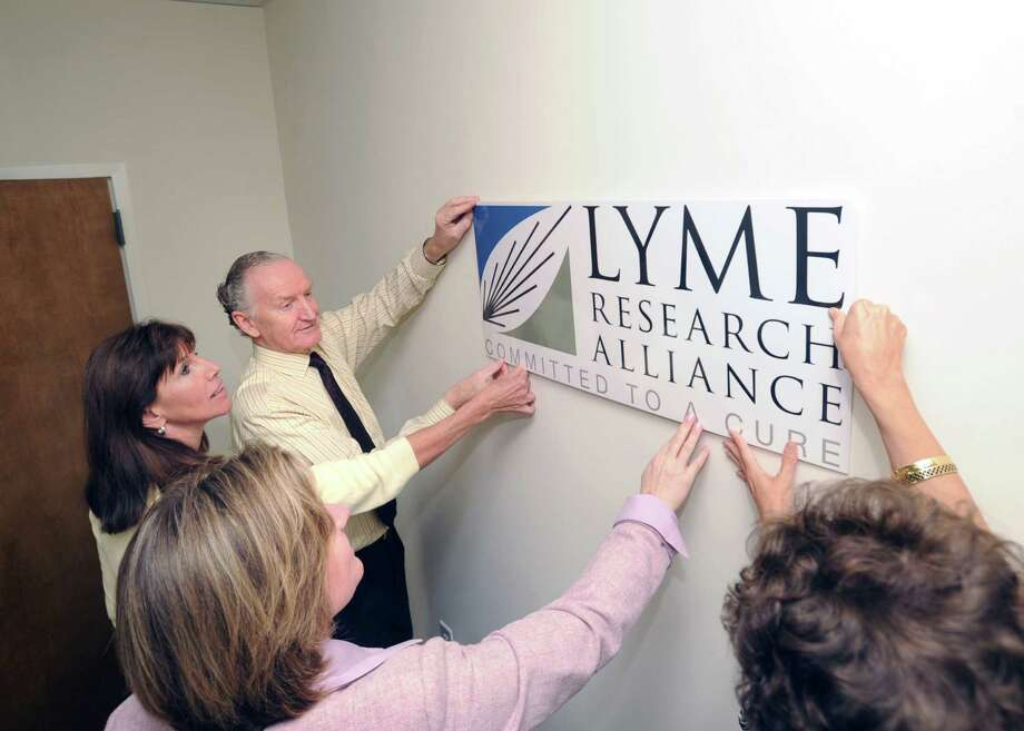 Members of Lyme Research Alliance from top left, Executive Director Peter Wild and Greenwich residents, co-founders and executive committee members (from left) Fran Herzog, Debbie Siciliano and Diane Blanchard place their new logo on a wall in their Stamford office recently. The organization was previously named Time for Lyme, but has changed its name to more accurately reflect its mission to fund and promote research and education about Lyme and other tick-borne diseases. Photo: Bob Luckey / Greenwich Time