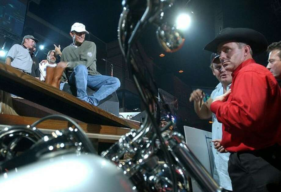 "San Antonio country singer George Strait, top, reaches for his boots which he included with a Harley Davidson motorcycle as Shane Davis, right, looks over the bike that we won in auction during the ""For the Love of Kids and Harleys"" fundraiser at Far West Rodeo on Tuesday, Oct. 22, 2002. With Strait onstage are the five founders of the event: John Peveto, Larry Walker, Fully Clingman, Bill Miller and Hal Gottsacker."