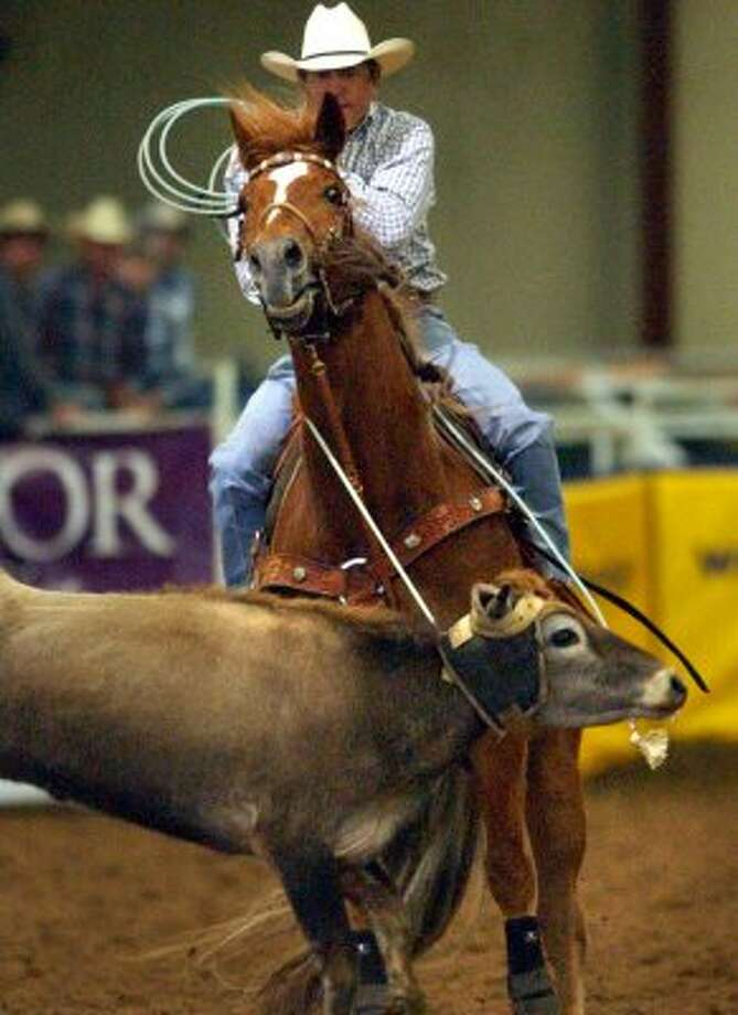 Country singer George Strait pulls back after roping a steer during the George Strait Team Roping Classic held at the Rose Palace in Leon Springs, Friday, Mar. 19, 2004.
