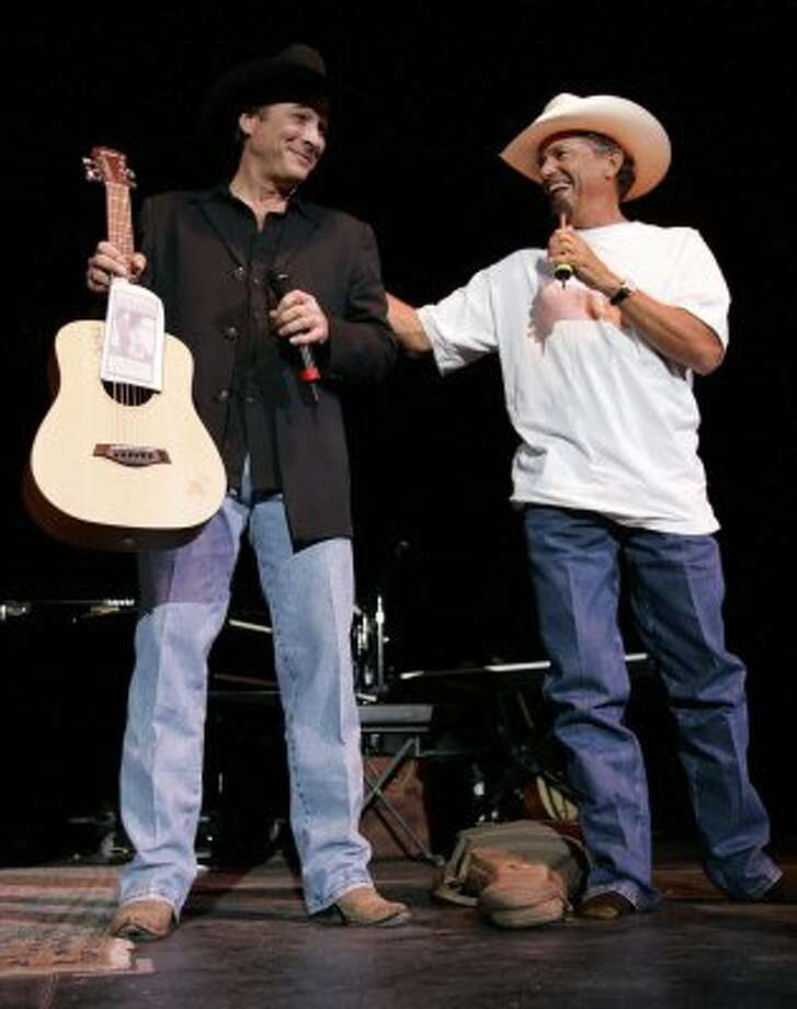 "George Strait, right, acts as a celebrity auctioneer Wednesday night Sept. 7, 2005 at the ""For the Love of Kids and Harleys"" charity concert as he helps auction a guitar donated by Clint Black, left, who headlined the concert. Strait donated the shirt off his back for the auction and the boots off his feet leaving him in a t-shirt and socks."