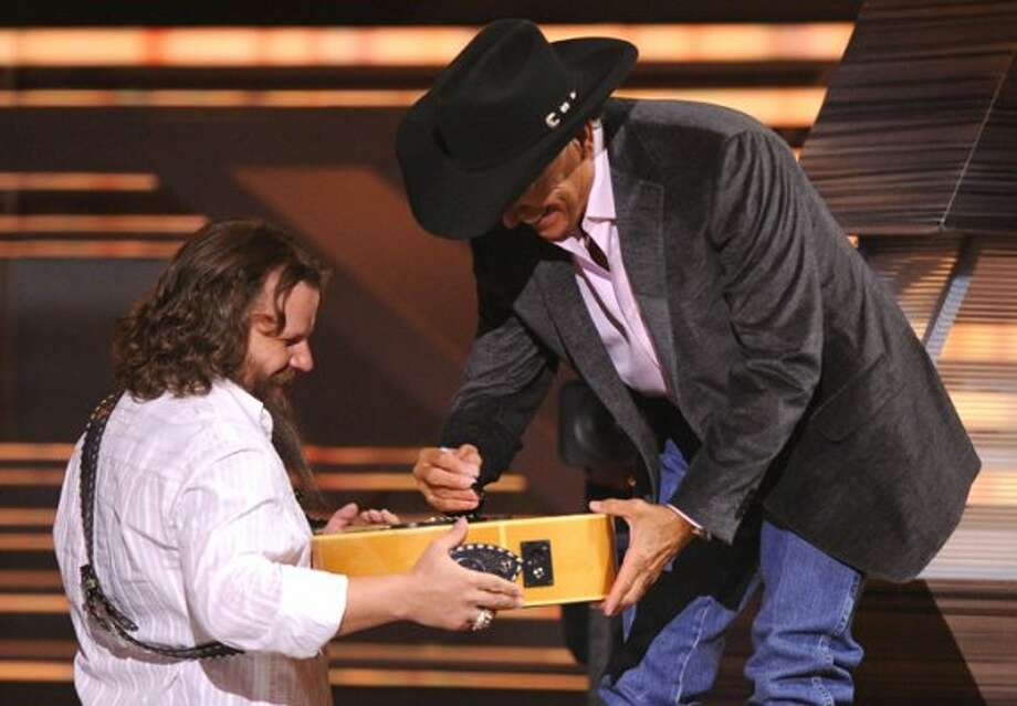 George Strait , right, signs an autograph for performer Jamey Johnson at the ACM Artist of the Decade All Star Concert, 2009.  George Strait is the recipient of the Artist of the Decade award.